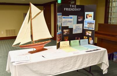Photo of a FriendShip informational table set up at an event with flyers and organizational information.