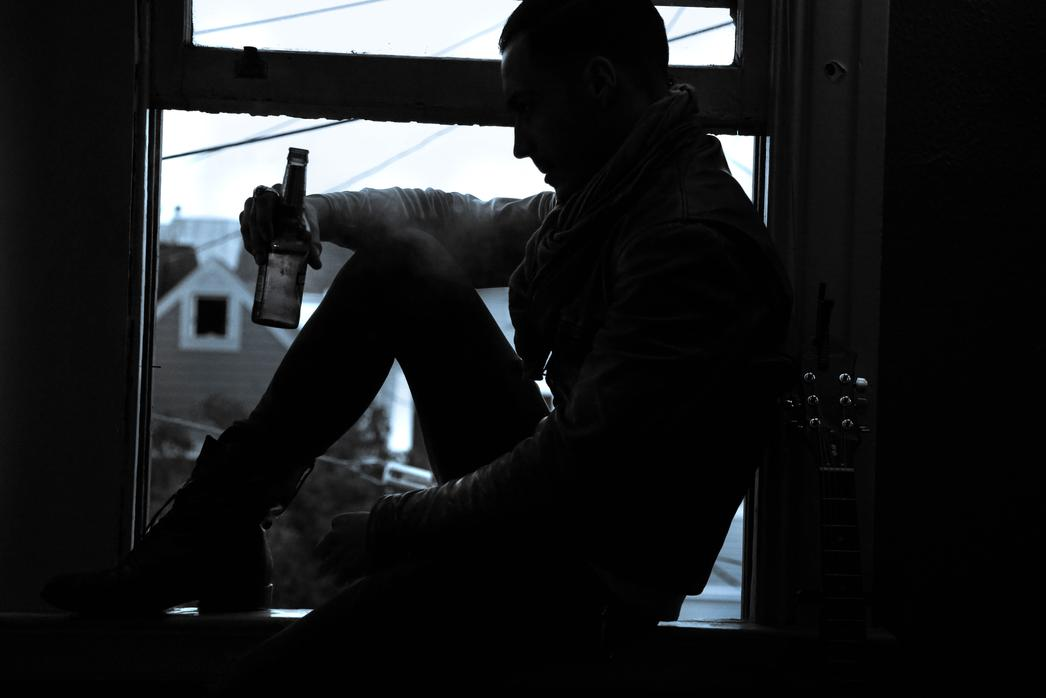 young man on window with guitar holding beer black and white