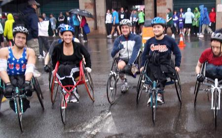 5 people wearing helmets and posing for a photo in track racing wheelchairs