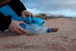 person picking up a plastic water bottle on the beach