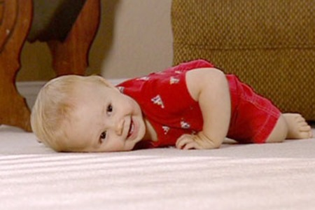 Baby smiling and laying on carpet