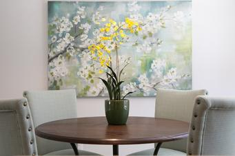 Staging can be simple! A large piece of art, upholstered chairs and a pop of color make this eat-in kitchen welcoming.