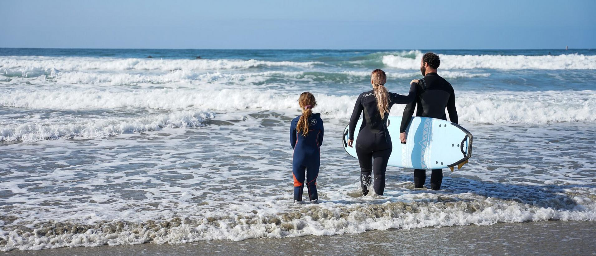Picture of a people about to go surfing, a man holding a surfboard with a women holding his shoulder with a young girl all standing in the whitewater as waves roll in towards them.
