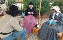 Three Re-enactors sitting and crafting at the Yule Festival