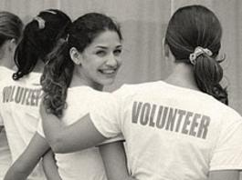 women embracing with volunteer shirts
