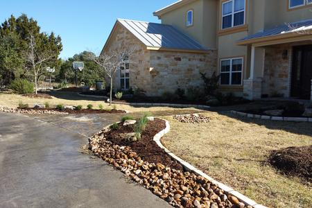 A landscaping project in San Antonio Texas from Wilson Landscape of a Beautiful Chop-Stone Rock Border with mulched beds and river rock curving around the driveway