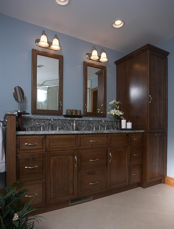 Beautiful Showplace cabinets with framed mirrors and topped with granite countertops
