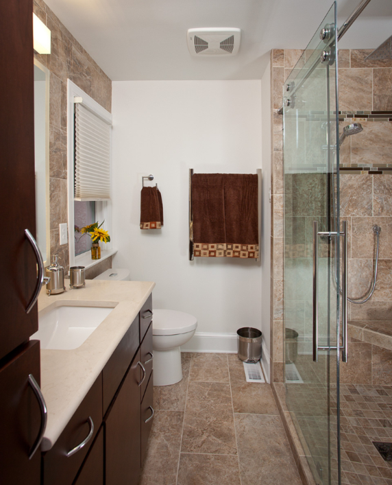 Guest bathroom with new vanities, custom tile shower with corner bench seat and rolling glass shower door