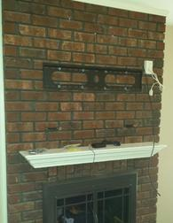 Flat screen tv mounted on brick fireplace wires installed through the brick, tv mounting service, flat screen tv mounting, charlotte nc