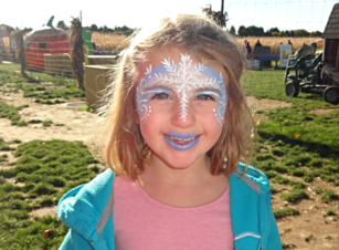 A young girl with a snowflake crown painted on her forehead and blue lipstick.
