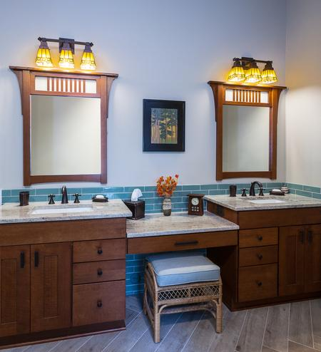 Double vanity with framed mirrors and a sitting area
