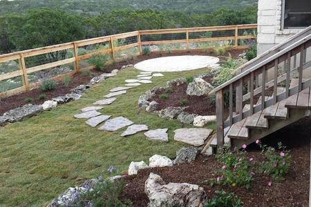 A landscape design by wilson landscape in San Antonio texas of a flagstone pathway leading to an existing set of wooden stairs and a flowerbed with pink flowers on the right and left hand side