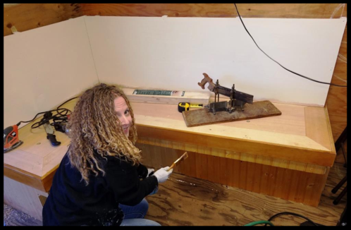 Heather Rinker applies the finishing touches on the benches in the classroom.