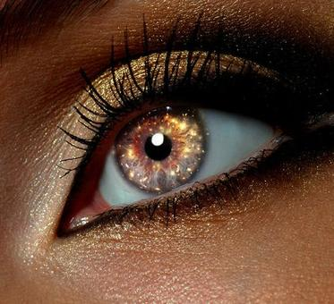 Close up view of a woman's gold shimmering eye looking into the distance