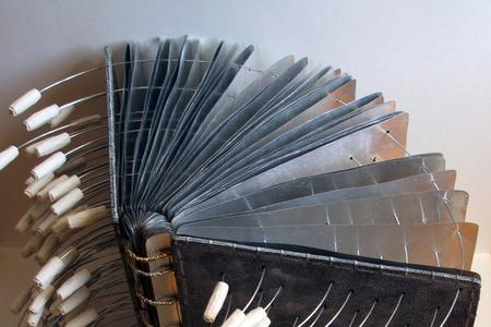 "Detail of sculpture/book Faithful Conversation, by Heejung Kim. Image shows ""book pages' made of metal; pierces with circular wires."