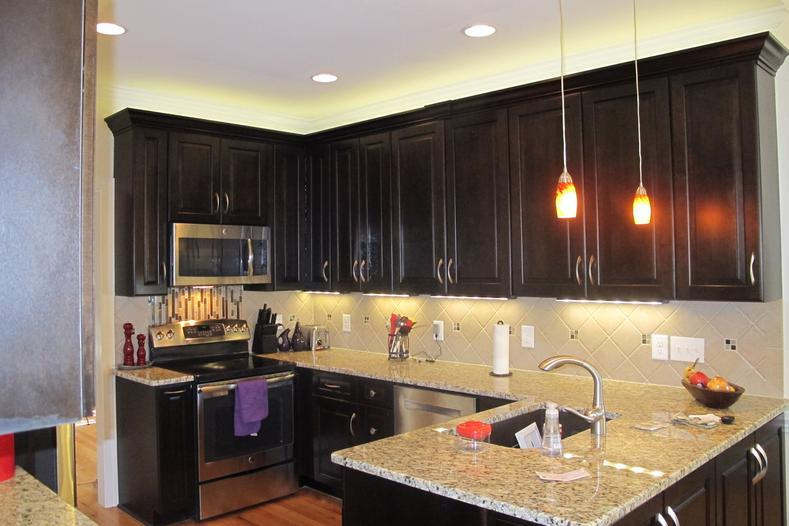 Beautiful cabinetry topped with granite countertops accented by stainless steel appliances