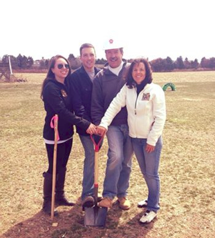 A Photo of Hank, his wife, son and daughter the day they broke ground on the market at Hank's PumpkinTown