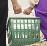 Image of green groceries basket being carried by two older adults.
