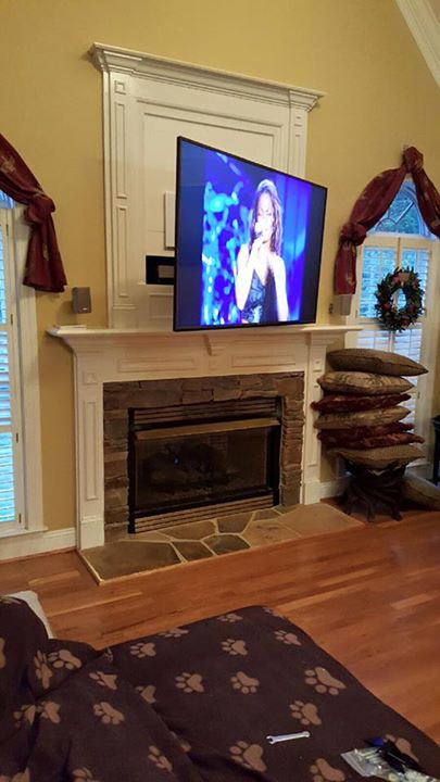 Make that outdated hole above fireplace vanish by installing a flat screen TV covering it. Custom TV mounting over fireplace niche