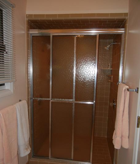 Dark and dreary entrance into the old shower stall with sliding doors before remodel