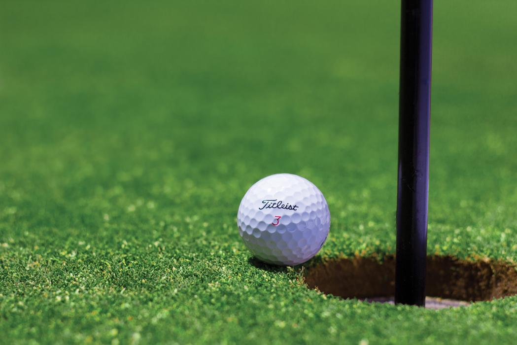 background image of a golf ball on the edge of the Hole one the golf green with flag still in the hole.