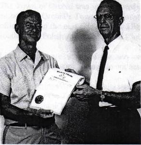 Image of Mr. Joe Michael accepting the town's charter from Arthur Karst
