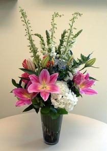 Vase arrangement designed with pink lilies, white hydrangea, multi-colored roses, delphinium, and a variety of foliage