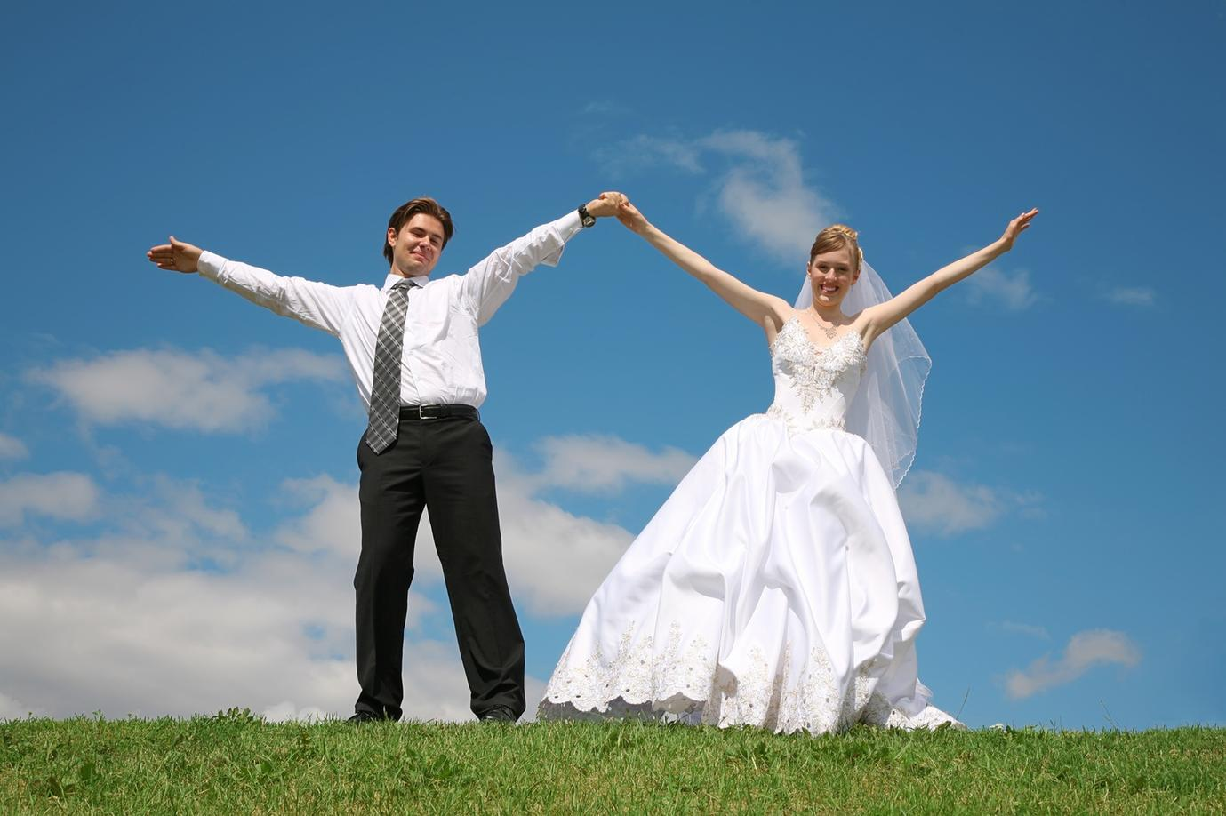 Bride and Groom on their wedding day. Groom is wearing a suit, Brides is wearing a beautiful white wedding dress.