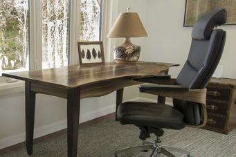 Office in cottage with black leather chair at live edge desk with birch tree lamp