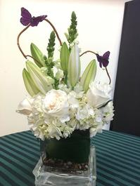 Whimsical white vase arrangement including roses, hydrangea, oriental lilies and snapdragon designed in a 5'' glass vase accented with curly willow and butterflies