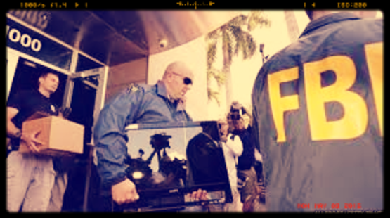 photo from low angle under dark metal awning of deluxe office building. FBI agents, one in an emblemed t-shirt and beige chinos, others in blue windbreakers with patch on sleeve, carrying boxes and a wide-screen monitor from building, moving left to right. One large balding agent wears sunglasses. At right, back of agent whose windbreaker says FBI in yellow. In the background photographers and palm trees are just visible between them. Sepia toned colors, frame effect to look like video.