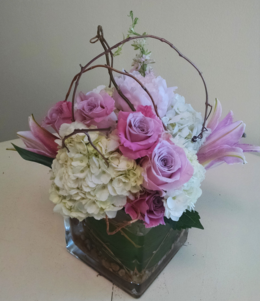 Vase arrangement designed with hydrangea, lilies, roses, curly willow, and a variety of foliage