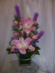 Vase arrangement designed with pink oriental lilies, purple liatris, pink spray roses, purple statice, and a variety of foliages