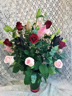 This bright and cheery vase arrangement is the perfect thing to brighten someone's day! Roses and lilies are designed in an extravagant clear glass vase with pink gravel for the perfect arrangement!