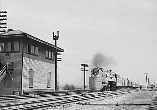 "Milwaukee Road class F7 streamlined steam locomotive (type 4-6-4) hauling the ""Midwest Hiawatha"" past Tower B17, Bensenville, Illinois, in May of 1943."