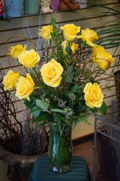 A dozen of astonishing yellow roses accented with beautiful green foliage designed in a graceful glass vase.