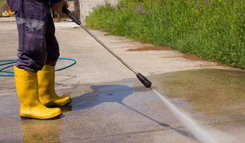 handy man using a pressure washer on a driveway
