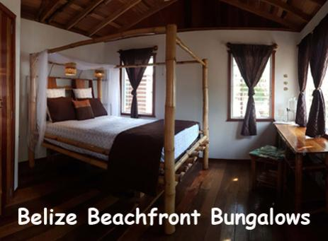 A queen sized bed made from bamboo sits in a beach side bungalow. Belize Beach Vacations