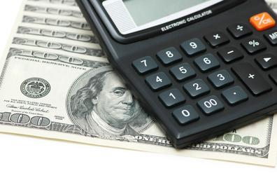 Calculator and one-hundred dollar bills image