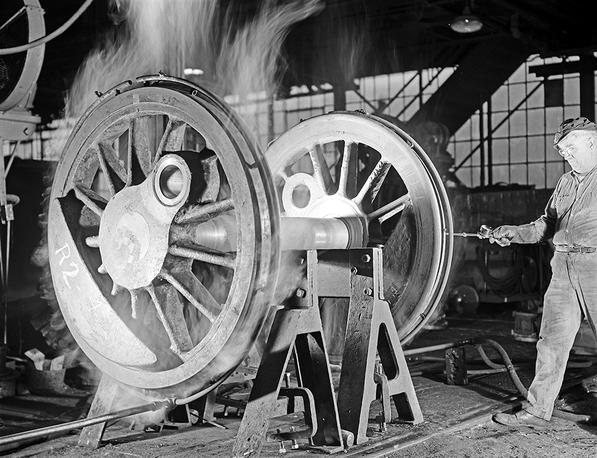 Machinist Checking Temperature of Locomotive Wheel, Texas & Pacific Railway Company] Creator: Richie, Robert Yarnall, 1908-1984 Date: ca. 1946.