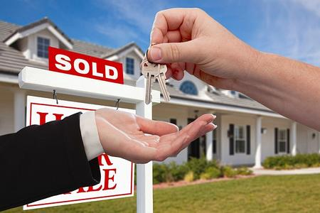 A man in front a home with a house for sale sign getting the keys to the house he just bought