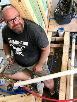 Photo of the master plumber sitting in a hole in a house floor installing new pipe, surrounded by tools.