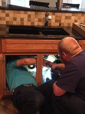 Plumber installing kitchen faucet in residential home in Lakeway Texas
