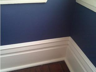 image of white baseboard painted with a sharp line against a dark blue wall