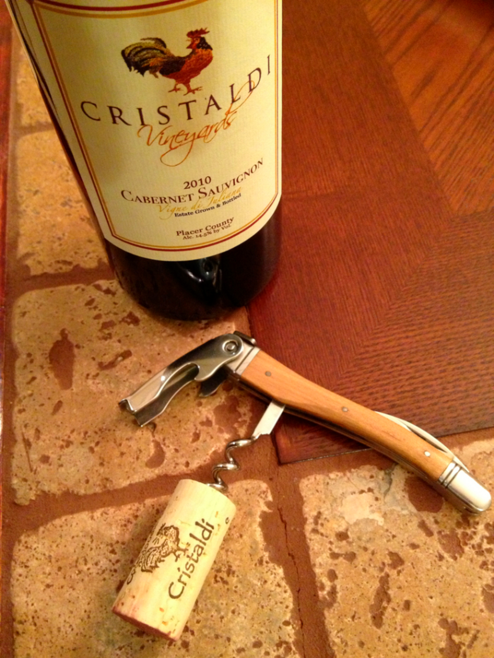 Photo of a bottle of Wine with corkscrew set on table