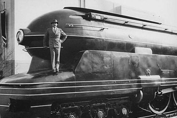 Industrial designer Raymond Loewy standing on one of his designs, the Pennsylvania Railroad's S1 steam locomotive.
