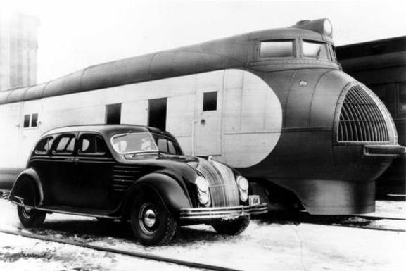 A streamlined automobile and streamlined trainset side-by-side.