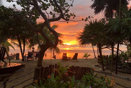A Belize sunrise over the Caribbean Sea on a beach dotted with coconut palms and seagrapes. Beach chairs are setup for viewing the scene. Enjoy your best Belize vacations at Leaning Palm Resort!