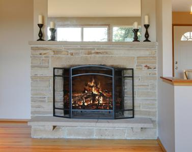 Photo of warm fireplace with glass fireplace screen and mirror