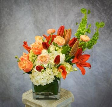 White hydrangea along with vibrant orange lilies are designed in a glass cube. Accents of orange roses and bright green bells of Ireland enhance the look.